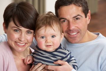 Portrait Of Proud Parents With Baby Son At Home