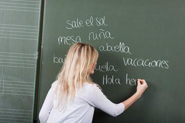 schülerin schreibt spanische vokabeln an die tafel
