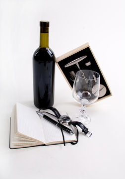 a bottle of wine with notebook, watch and wine accessories