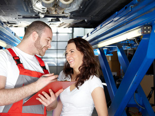 Motorcar mechanic explaining repair and maintenance costs