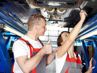 Motormechanic and apprentice are fixing a car