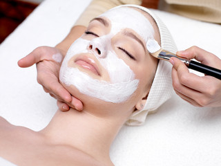 Woman receiving facial mask at beauty salon
