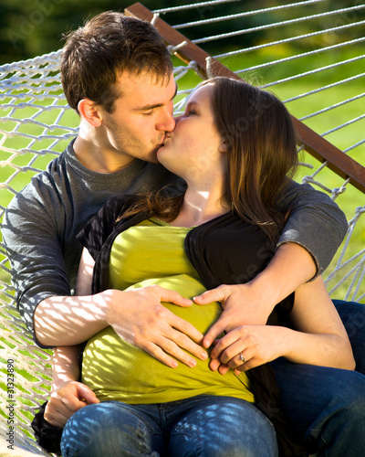 Young Expectant Husband And Wife Kissing