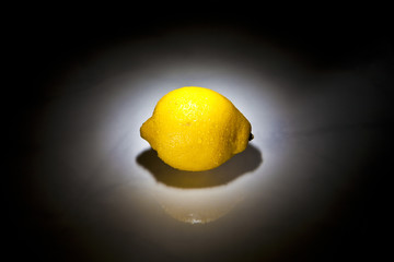 lemon in spotlight on black background