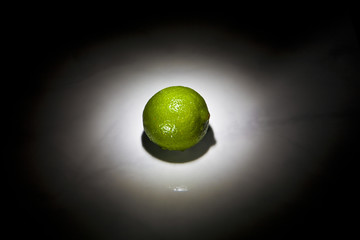 lime fruit in spotlight on black