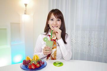 トロピカルジュースを持っている笑顔の女性