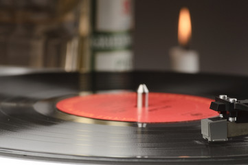 Old record player with a lit candle  in the background.