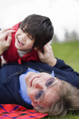 Father playing with disabled son on grass at park
