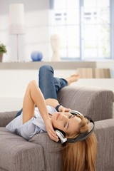 Attractive female laying on sofa listening music