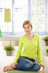 Attractive woman sitting at home in vivid green