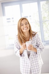 Young female laughing happily in pyjama