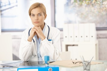 Young female doctor sitting at desk