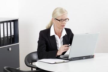 Frau am Schreibtisch mit Laptop erstaunt