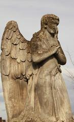 Figure of a praying angel on a blue sky