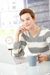 Young woman reading on laptop