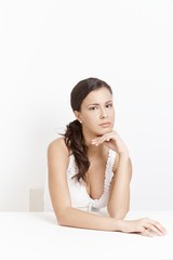 Sad girl sitting over white background