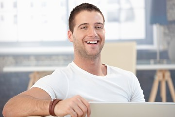 Young man laughing happily at home