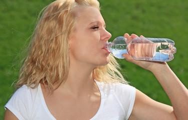 Attraktive Frau trinkt aus einer Wasserflasche