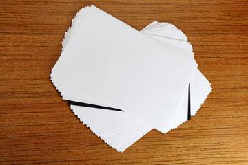 Стопка белой бумаги с контрастным черным листом внутри на столе.