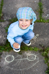 Portrait of cute little girl drawing a car on the ground