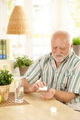 Senior man taking medication at home