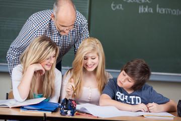 drei schüler mit lehrer im unterricht