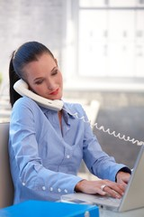 Businesswoman with laptop and landline phone