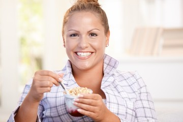 Pretty girl eating yoghurt at home dieting smiling
