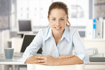 Young woman sitting at desk in office smiling