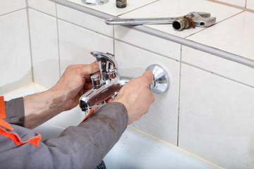Plumbers hands fixing water  tap in a bathroom