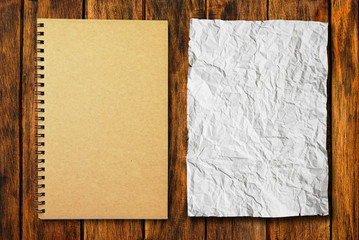 notebook with crumpled paper on wood background