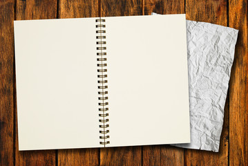 blank notebook with crumpled paper on wood background