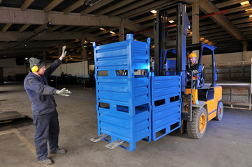 Worker helps forklift operator at factory.