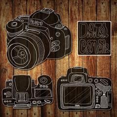 Digital camera drawing sketch on wood background