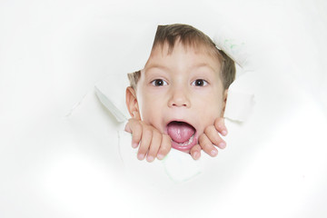 young boy shouting through hole in paper