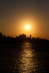 The sun setting over Havana with a silhouetted view of the city