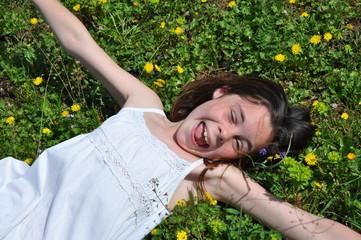 Fillette heureuse allongée dans les fleurs printemps