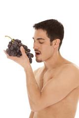Man eating grapes