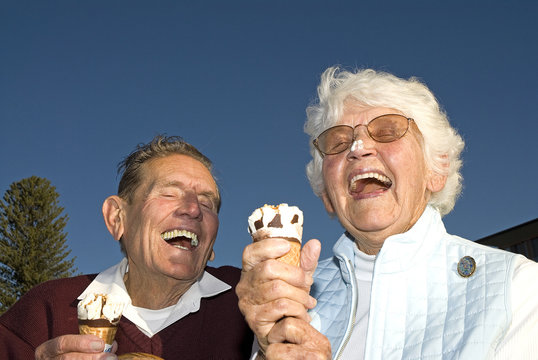 Elderly couple laughing at ice cream accident