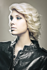 Beautiful young blond fashion model with leather jacket