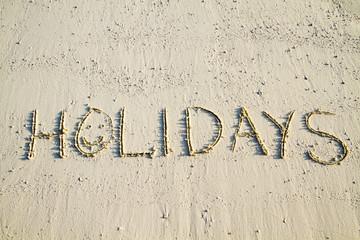 Holidays written in sand.