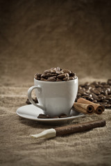 cup with coffee beans and cinnamon on burlap