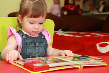 little girl in denim jumpsuit seats at table and read