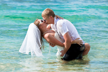 groom and bride kissing in the sea