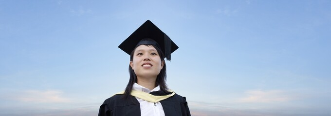 Happy asian lady graduate with panoramic sky background