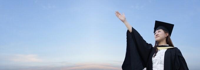 Asian lady graduate raising hand with panoramic sky