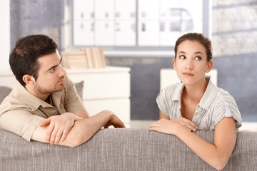 Young couple sitting on sofa in bad mood
