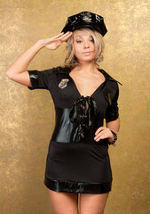sexy blonde woman in black police costume on golden background