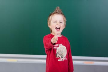 kindergartenkind vor der taqfel zeigt daumen hoch