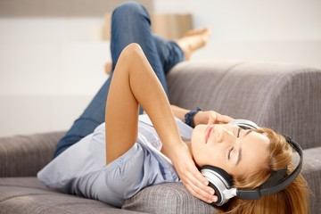Attractive girl enjoying music laying on sofa
